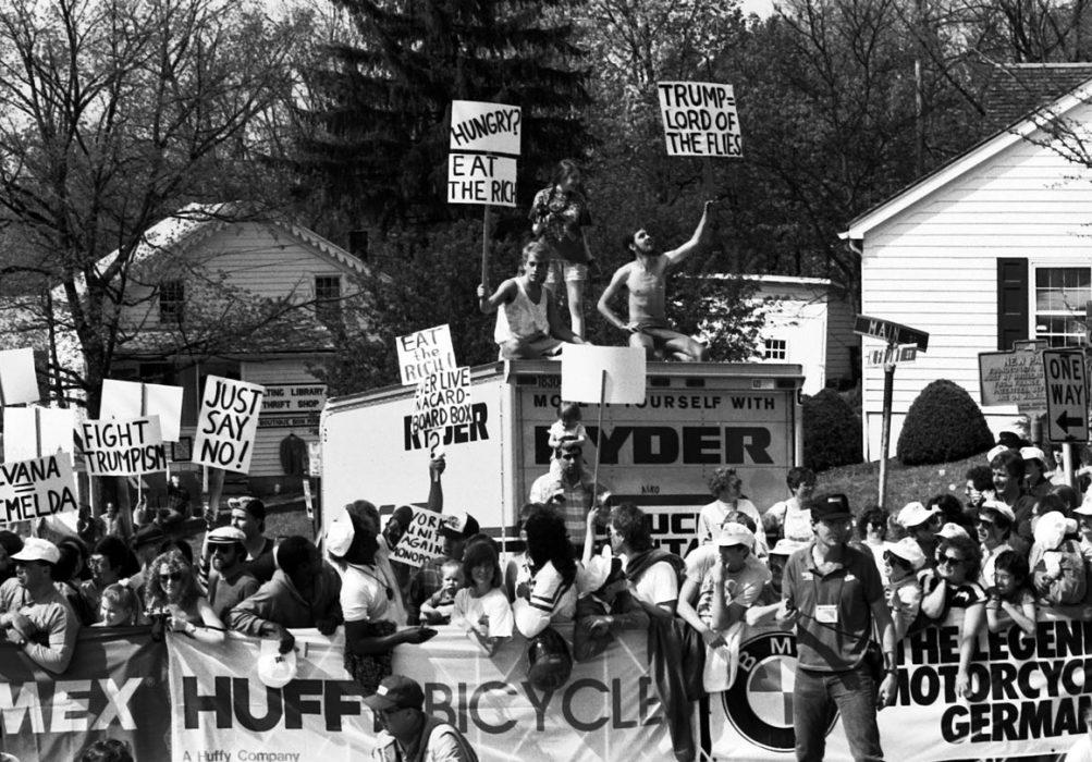 Διαδηλωτές κατά του Donald Trump και όλων όσων συμβόλιζε, το 1989, στον τερματισμό του πρώτου ετάπ του Tour De Trump.